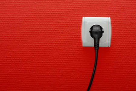 grounded plug: Electric socket on a red wall with connected cable