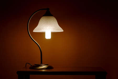 Small table lamp glowing in the dark photo