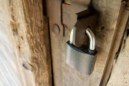 Padlock on an old wooden door photo