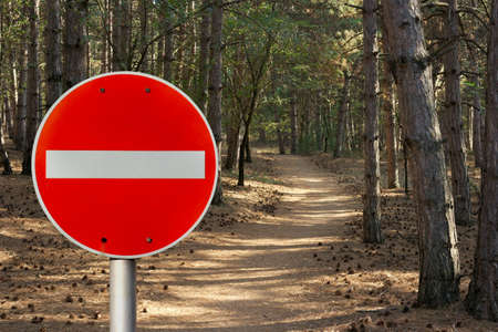 No entry sign in front of a forest path representing environmental protection photo