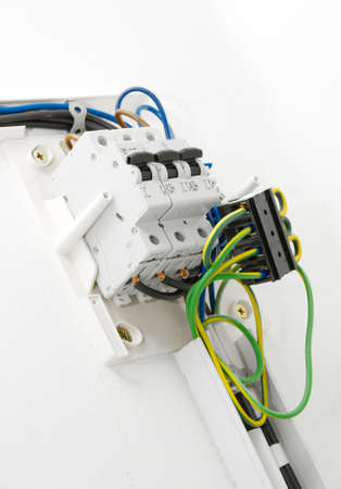 fusebox: Electric wiring on white wall in a house