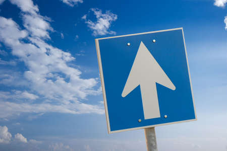 Arrow sign against bright blue sky with white clouds photo