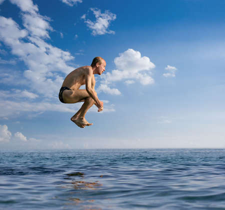 bombe: L'homme sautant dans la mer d'une hauteur Banque d'images