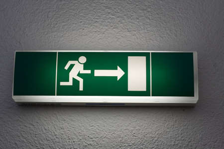 Emergency exit sign on white wall photo