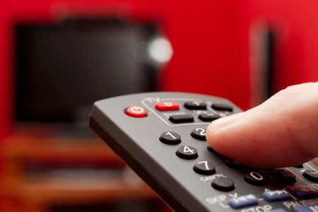Finger on the remote control of a TV photo