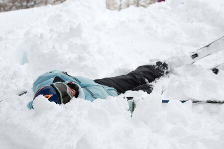 Female skier fallen into deep snow  photo