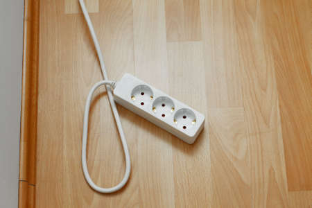Electric extension cords on the parquet photo