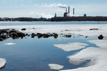 Smoking industrial plant and melting ice photo