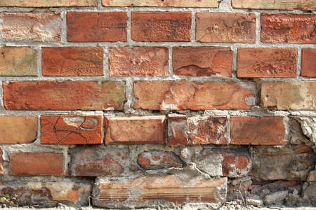 Aged brick wall texture with small red bricks photo