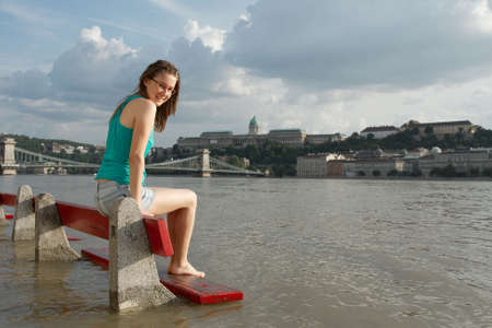 the danube: Girl sitting on a bench while the river Danube is flooding at Budapest