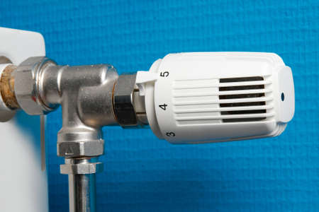 Closeup of a heating radiator against blue wall photo