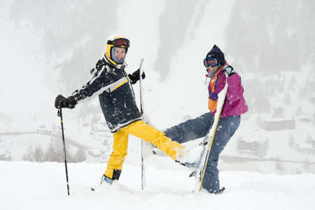 Young female skiers having fun in the falling snow photo