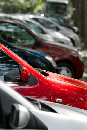 Row of parking cars, selective focus on the red one photo