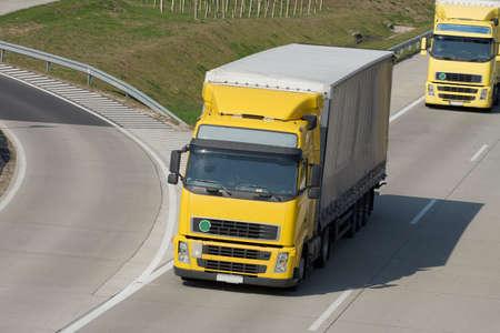 Yellow trucks roaring on the highway photo