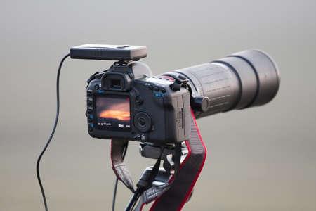 SLR camera on tripod with telephoto lens photo