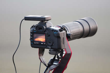 slr: SLR camera on tripod with telephoto lens