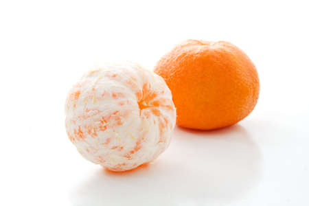 Closeup of tangerines, one in whole and one peeled photo