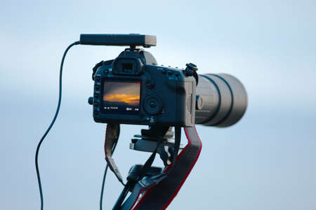 Modern DSLR camera with telephoto lens against soft blue sky Stock Photo - 6575728