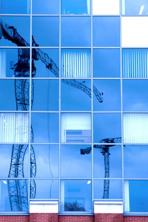 Reflection of a construction site in a glass office building photo
