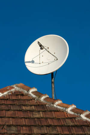 Parabola satellite receiver on a roof photo