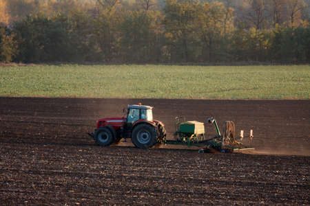 Tractor plowing the soil photo