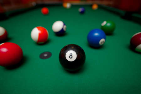 Pool table with the black ball in the middle photo