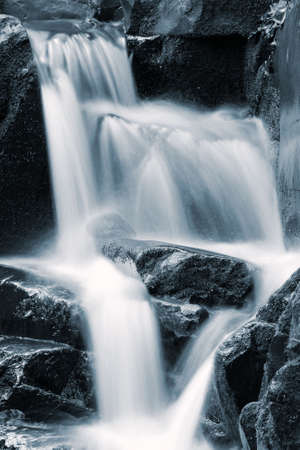 unspoilt: Waterfall rushing down the rocks, blue toning