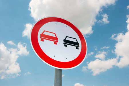 overtaking: No overtaking traffic sign against blue, cloudy sky