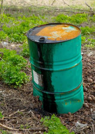 Leaking oil barrel left on a field photo