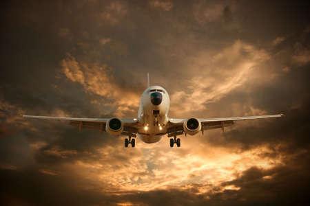 passenger vehicle: Landing airplane against glowing sky