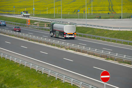 Highway with oil transporting truck, rapeseed field in the background photo