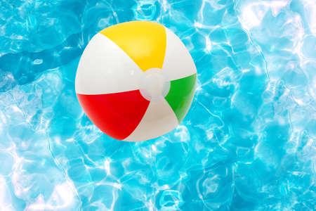 Pelota de playa sobre la superficie del agua de una piscina