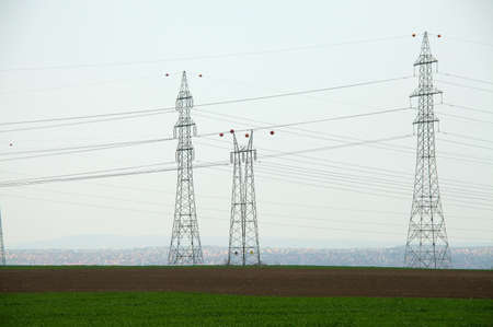 High voltage electricity lines across a field photo
