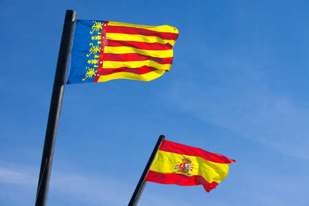 Flag of Spain and Valencia against blue sky photo