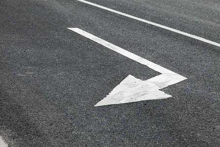 Arrow sign on the asphalt road photo