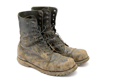 combat boots: Muddy boots isolated on white background