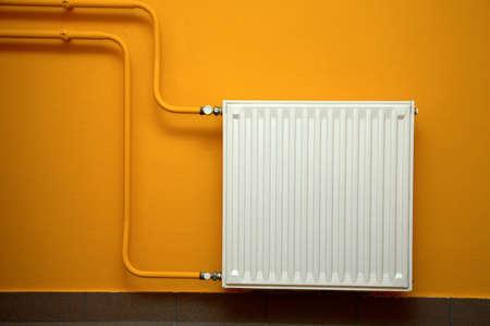 Heating radiator, orange wall Stock Photo