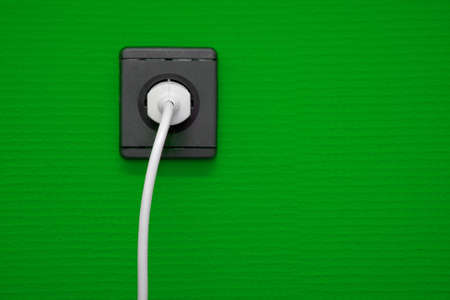Electric outlet on green wall with cable connected photo