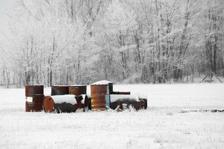 hazardous waste: Abandoned, rusty oil barrels in the snow