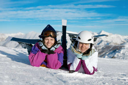Happy female skiers resting in the snow photo
