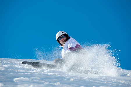 Female skier coming down the slope Stock Photo