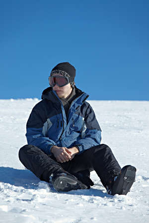 Skier resting sitting in the snow photo