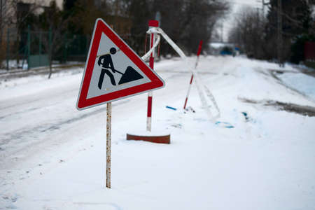 Road construction sign on a snowy street photo