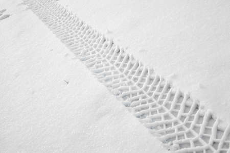 Trail of wheel in fresh snow photo
