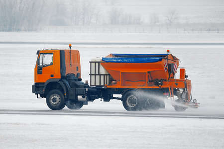 Truck deicing a road in winter