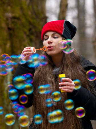 Woman blowing bubbles outdoors photo