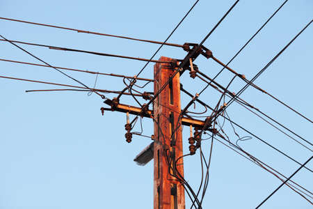 Old, rusty electric line against blue sky Stock Photo - 12650940