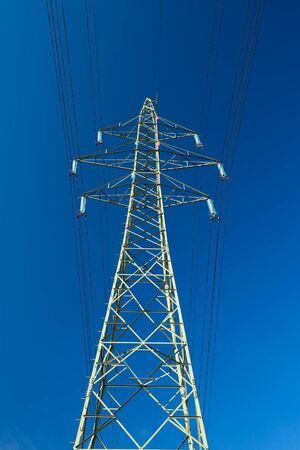 High voltage electric line against blue sky photo