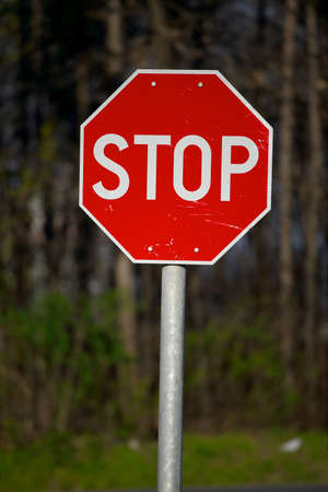 sign plate: Stop sign closeup with woods in the background Stock Photo
