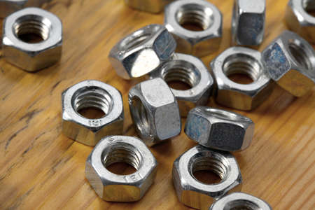 A pile of metal nuts on a table photo